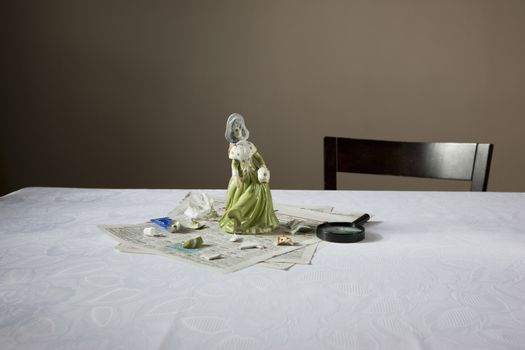 Closeup of a figurine with magnifying glass and papers on table