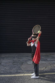 Boy wearing Zorro costume with tennis racket
