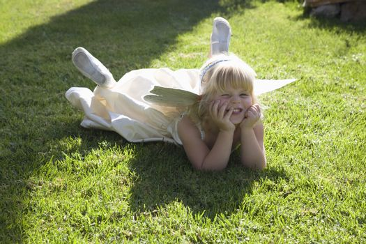 Girl with head in hands lying on grass