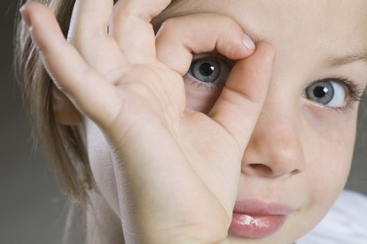 Studio portrait of girl peeking through hand close-up