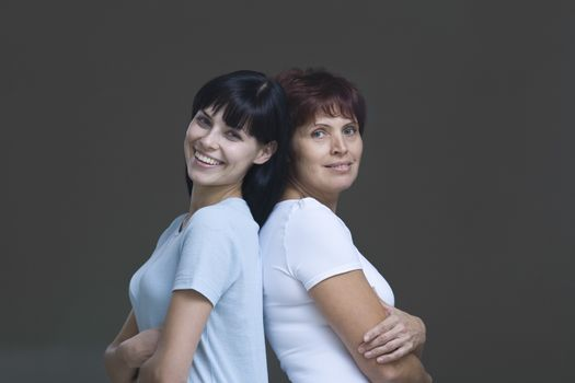 Studio portrait of young woman and mother back to back
