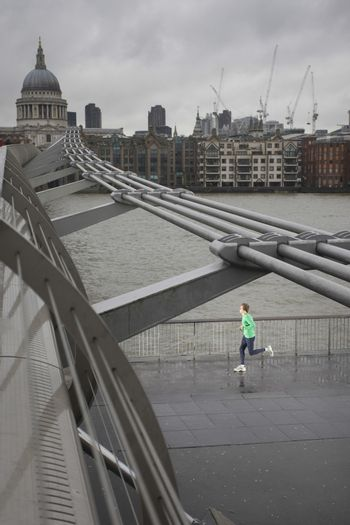 Elevated view of a young man jogging on bridge
