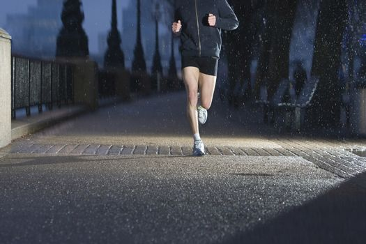 Young man jogging on city pavement at dawn in London