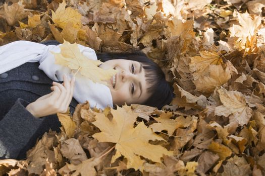 Woman lying on leaves in park