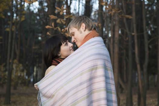 Young couple wrapped in blanket embracing in forest