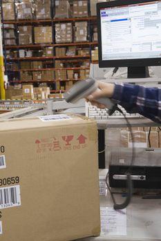 Man scanning bar code in distribution warehouse