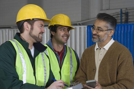 Cheerful men talking in factory