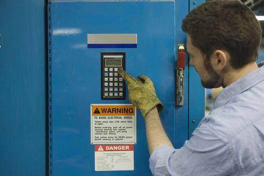Closeup of a man pressing keypad in newspaper factory