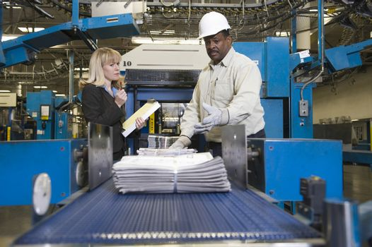 Man working on newspaper production line in newspaper factory