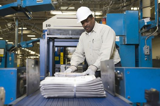 Side view of a man working on newspaper production line in newspaper factory