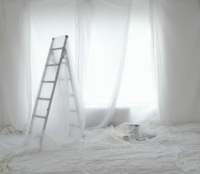 Empty room covered in dust sheets prepared for painting and decorating