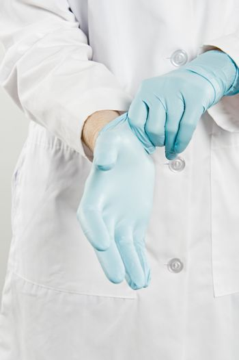 Midsection of a female doctor wearing rubber glove