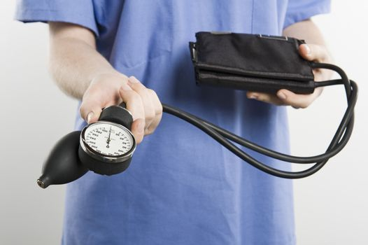 Midsection of a surgeon with blood pressure gauge isolated over white background