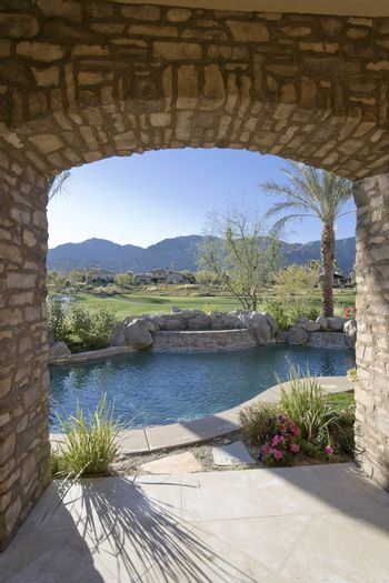 Arch overviewing swimming pool by luxurious residence