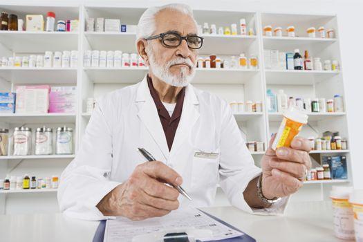 Senior male pharmacist working in pharmacy