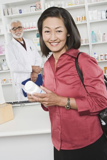 Woman picking up prescription drugs at pharmacy
