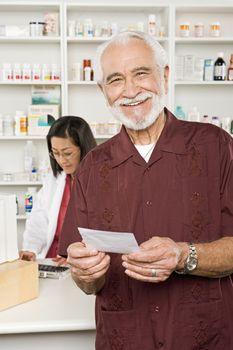 Man picking up prescription drugs at pharmacy