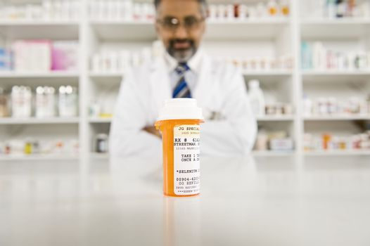 Prescription drugs with a male pharmacist in the background