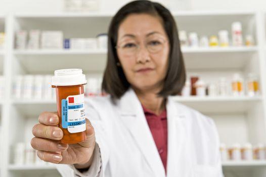 Portrait of a female pharmacist holding out prescription drugs