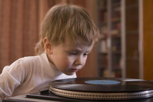 Closeup of a boy looking at vinyl record at home