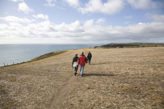 Three adults walk along a coastal cliff