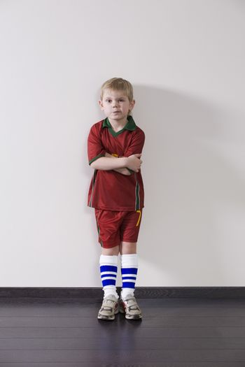 Boy wearing sports clothing leaning ageist wall