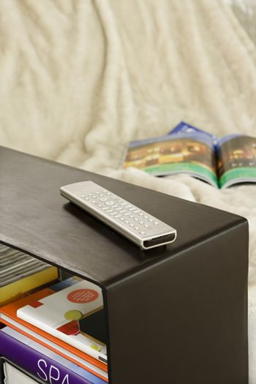 Closeup of a remote control on bookshelf