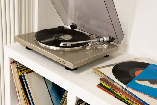 Closeup of a gramophone over shelf with vinyl records