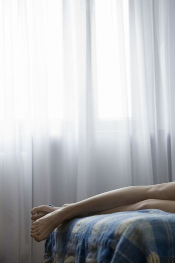 Woman lying on bed low section