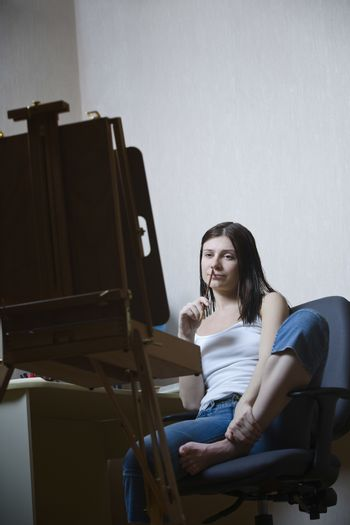 Woman sitting in front of easel