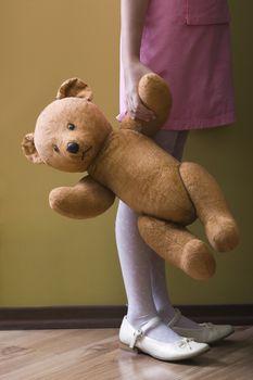 Girl holding teddy bear in home