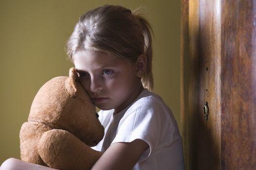 Girl embracing teddy bear in home