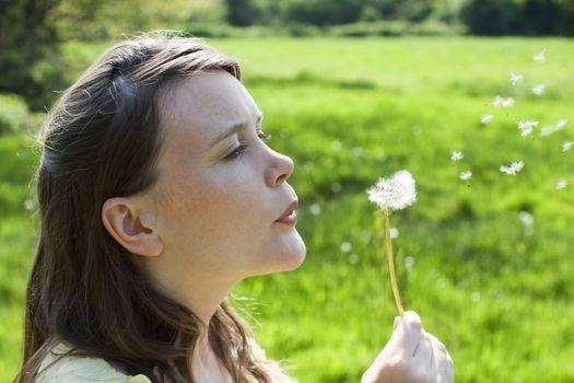 Woman blowing dandelion seeds