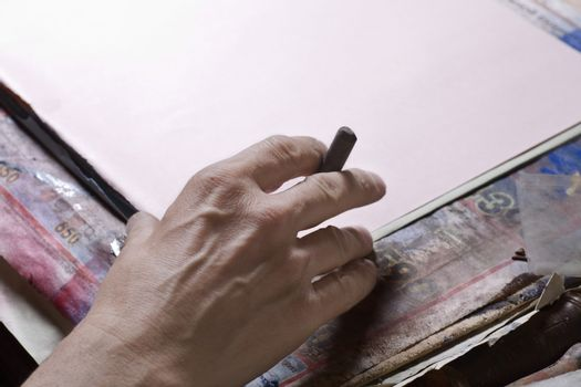 Closeup of a man's hand preparing to draw on board