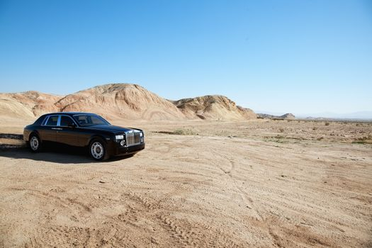Rolls Royce car leaving trail of black oil behind on unpaved road