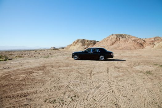Rolls Royce car parked on unpaved road with tire tracks