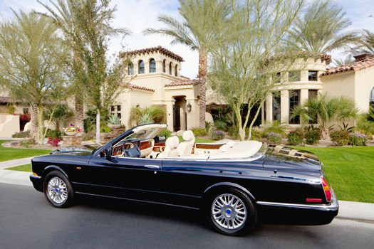 Black convertible car parked in front f luxury house
