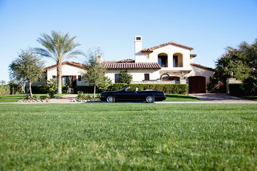 Luxurious car parked outside house in front yard
