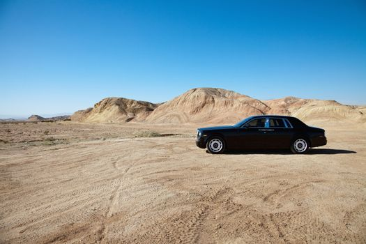 Luxury car parked on unpaved road near mountains