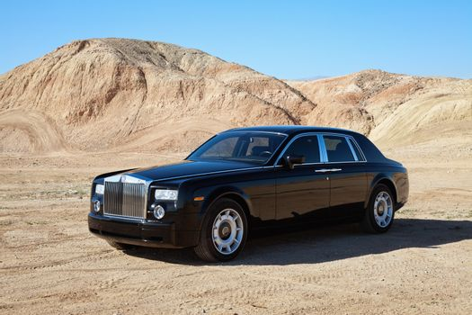 Rolls Royce car parked on unpaved road in front of mountains