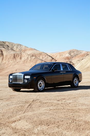 Rolls Royce parked on unpaved road with clear sky