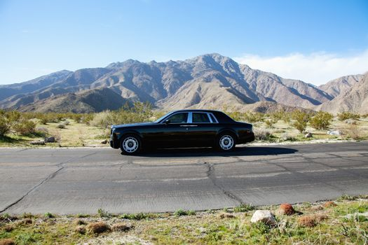 Rolls Royce travelling on country road with mountains in background