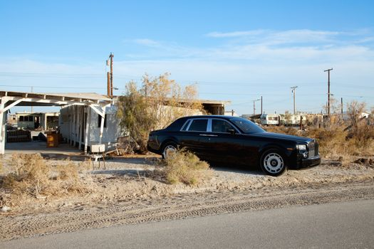 Rolls Royce parked on side of road near abandoned houses