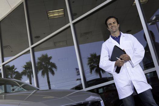 Happy car dealer standing in front of car showroom