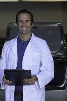 Portrait of smiling car salesman holding clipboard