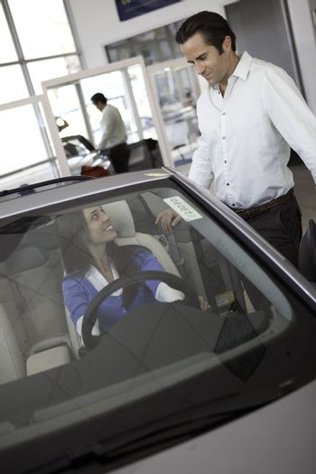 Woman sitting in car with husband standing besides the car