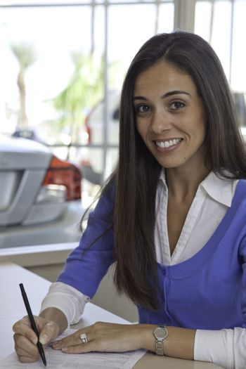 Portrait of woman signing papers