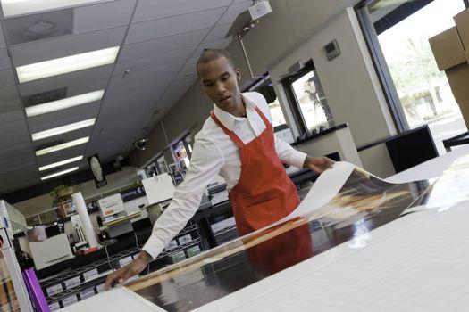 Manual worker taking large printouts