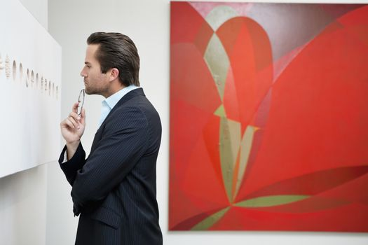 Profile view of a young man in a art art gallery