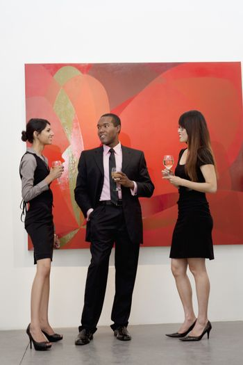 Young executives having a conversation in front of painting in art gallery